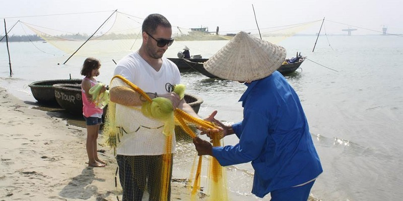 Турист и рыбак с сетью на берегу реки