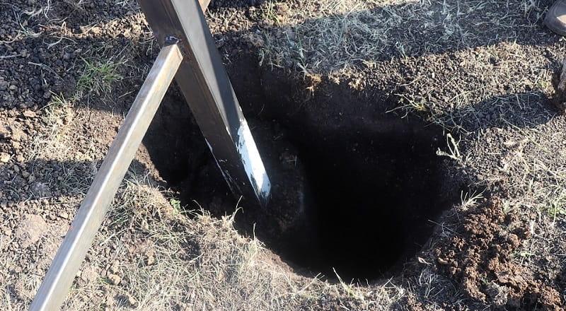 Отверстие в земле рядом с бетонным основанием профильного столба