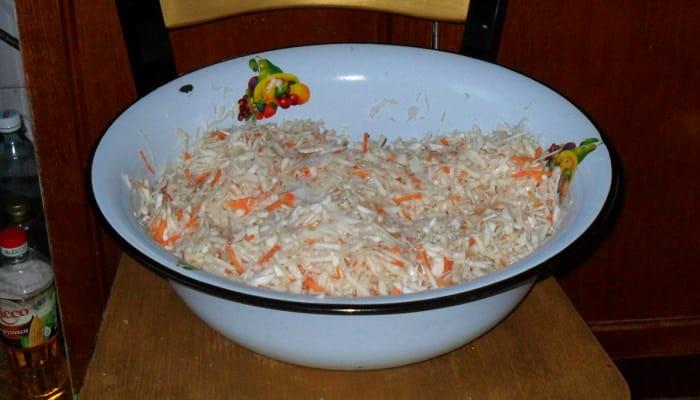 Капуста шинкованная с добавлением соли и моркови в тазу