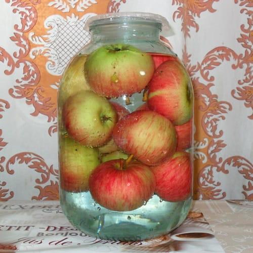 Свежие яблоки в трехлитровой банке, залитые рассолом